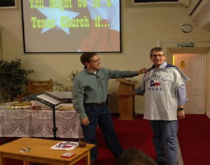 Revd John Singleton is presented with Texan T-shirt