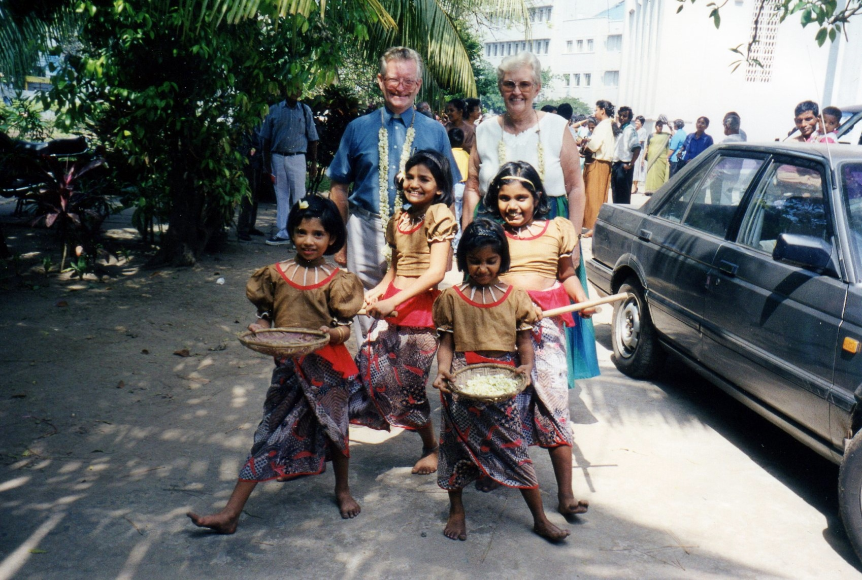 Western couple with four colourfully dressed Sri Lankan children